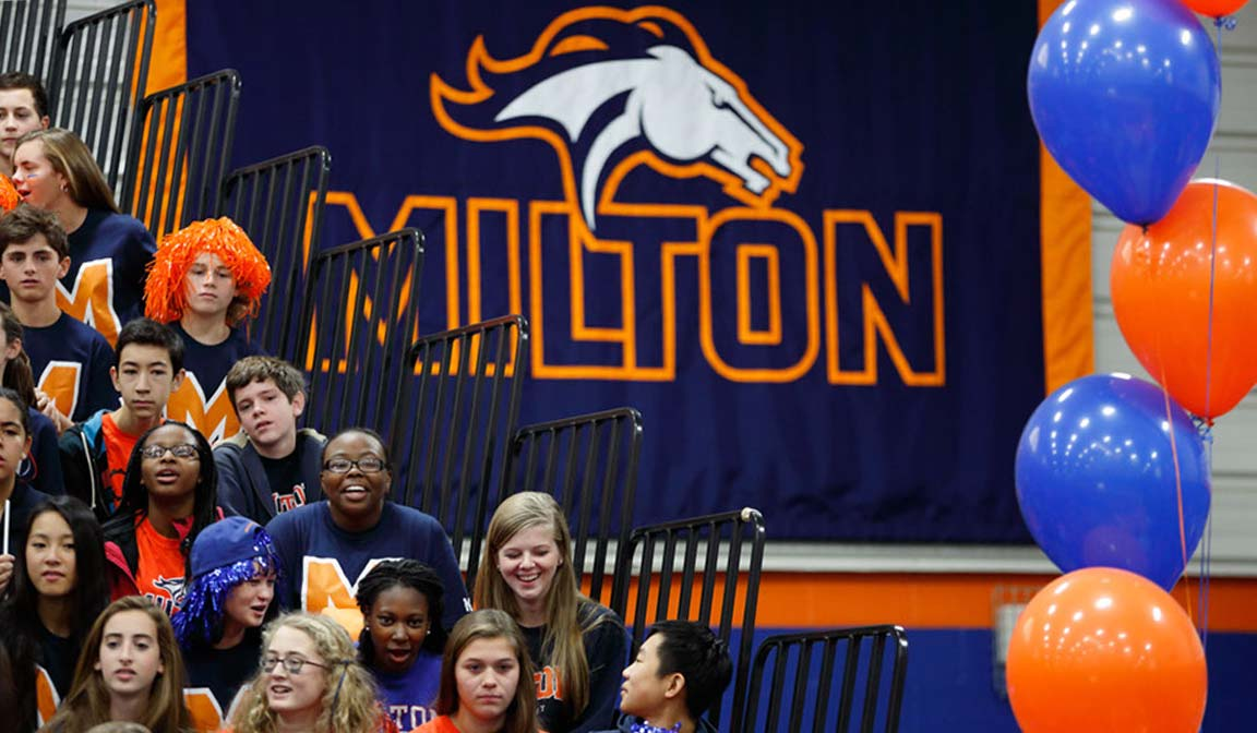 Milton Mustang sports branding logo and typography applied to a banner at a sporting event.