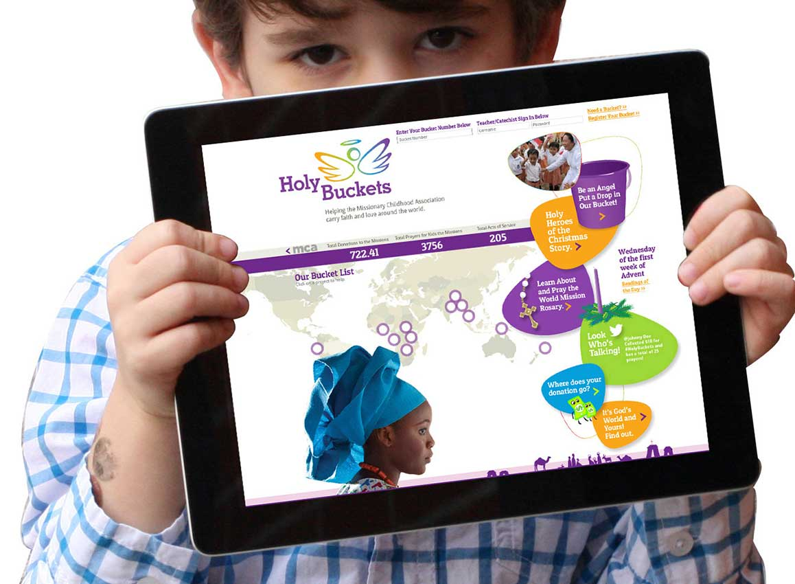 Young boy holding an iPad showing the website design for Holy Buckets, an awareness and fundraising program, created for the nonprofit organization Missionary Childhood Association.